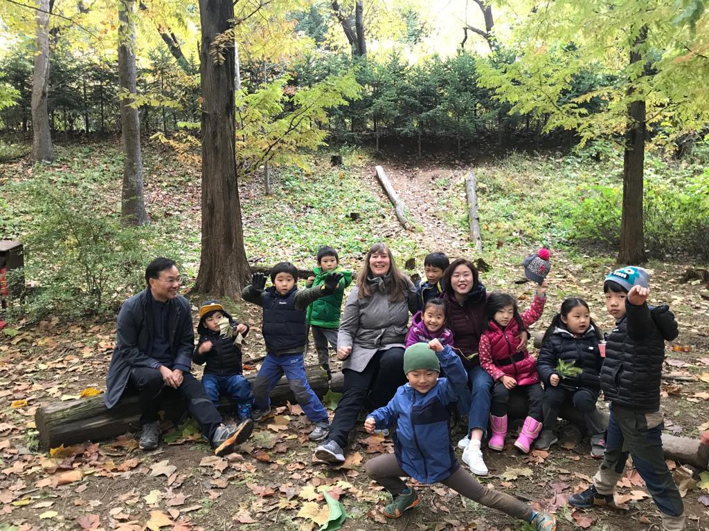Petra Jäger mit Prof. Dr. Lee inmitten der Kinder vom Waldkindergarten «Traumplatz der Waldkinder»