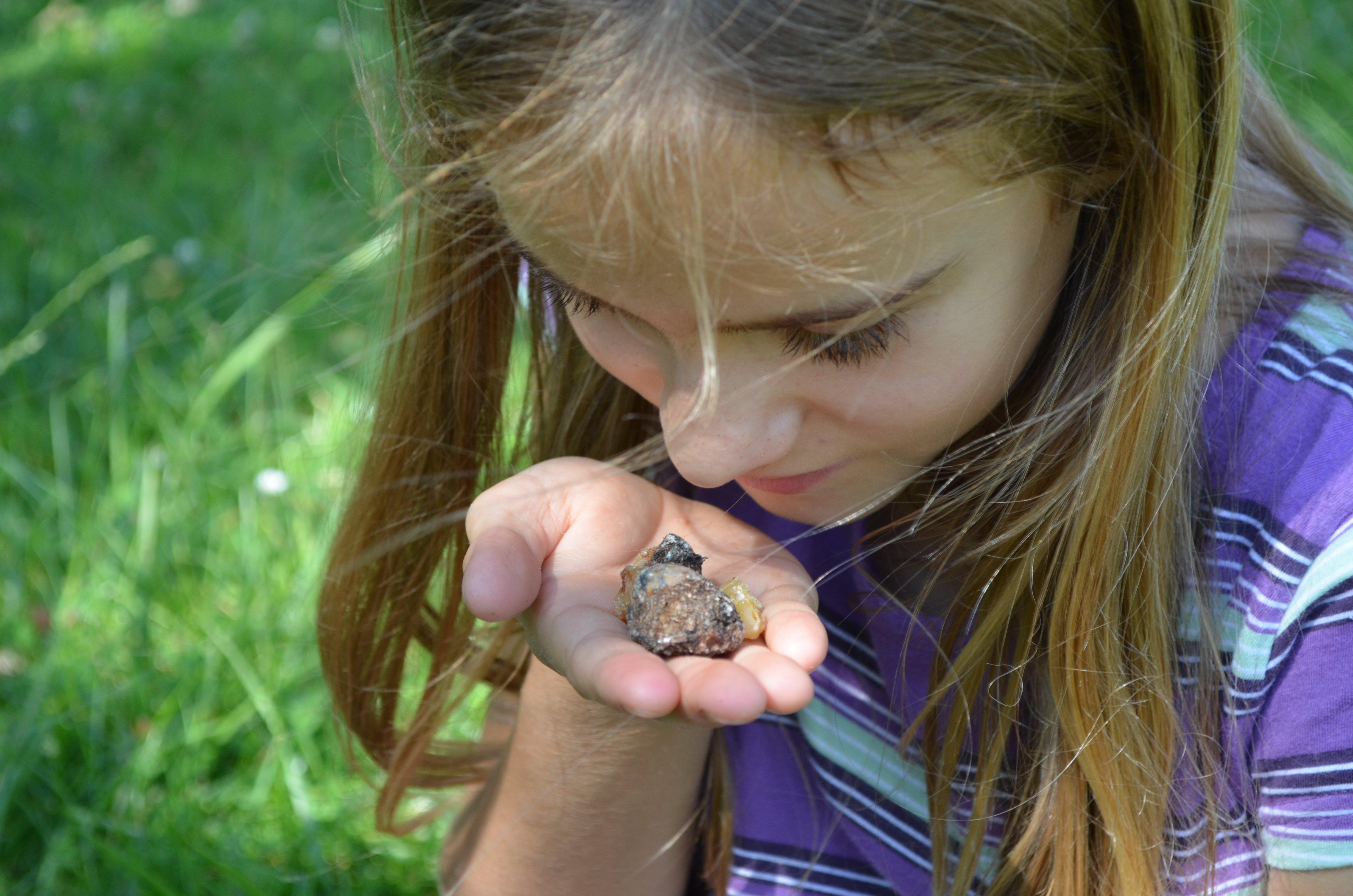 Das Mädchen riecht an einem Fichtenharz. Bei Kindern kann man beobachten, dass das tiefe Urwissen schneller aufbricht, das tief in uns allen verschüttet liegt.