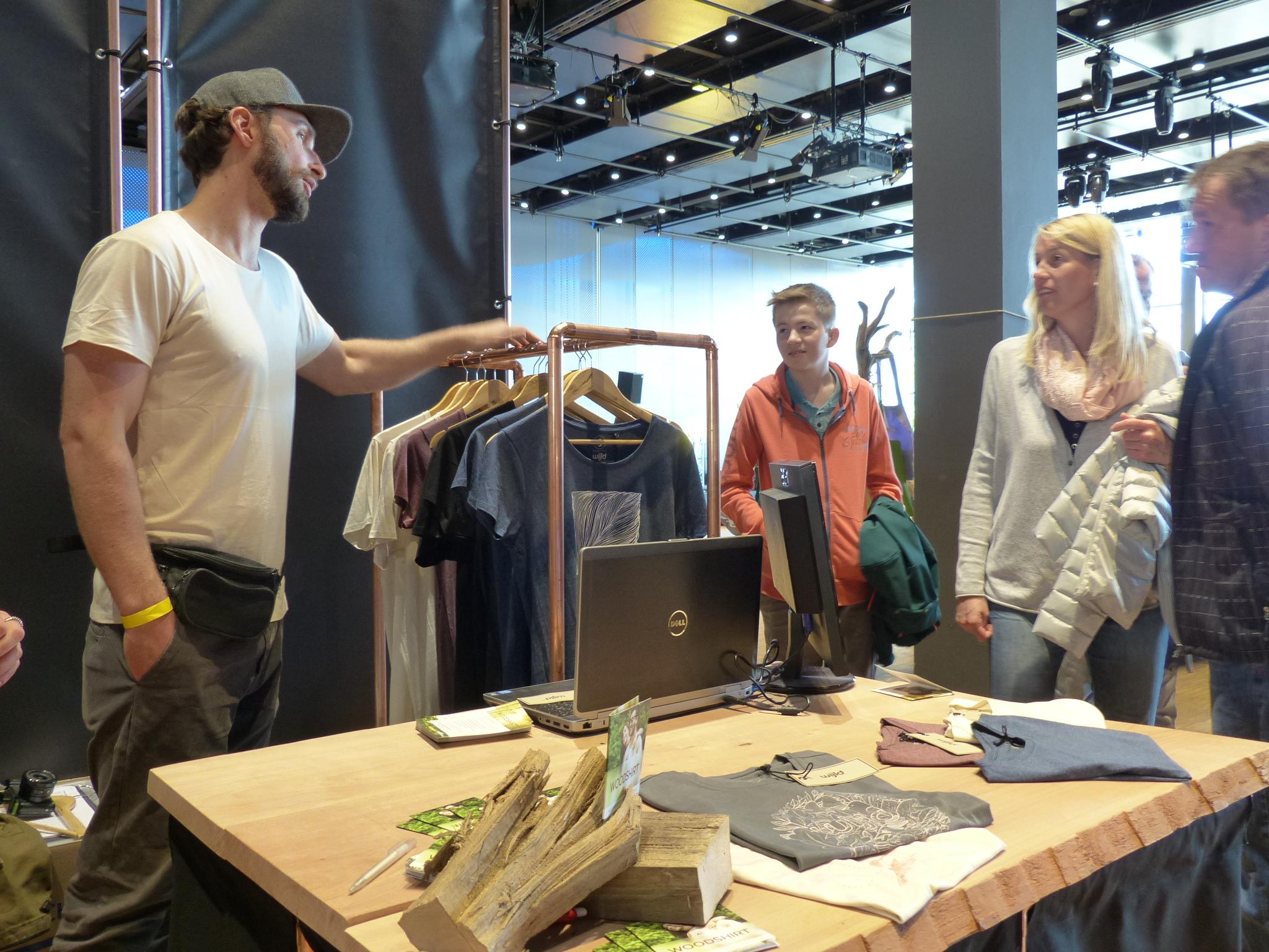 Interessierte Besucher durch alle Altersklassen blieben neugierig an dem Messestand stehen. Timo Beelow erklärt den Interessierten an der Messe den Produktionsweg der WoodShirt.
