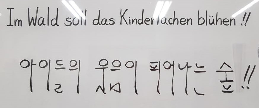 """The motto """"Children's laughter shall blossom in the forest""""  of the Waldkindergarten written in Korean characters"""