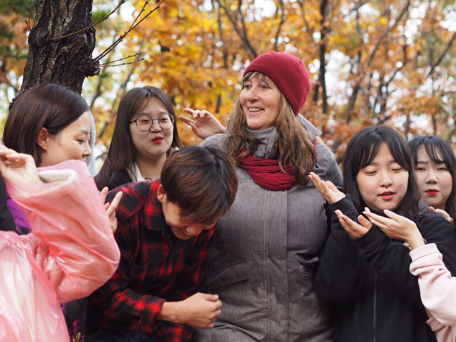 """Petra Jäger mit einer Gruppe Teilnehmer an dem Kongress """"Natur, Freispiel, Gemeinschaft"""", College Chung Kang, nach einer Stunde Dauerregen konnten die Regenschirme weggelassen werden"""